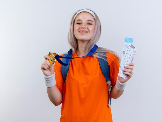 Lächelndes junges kaukasisches sportliches mädchen mit goldmedaille um den hals, das rucksackstirnband und armbänder trägt, hält flugtickets