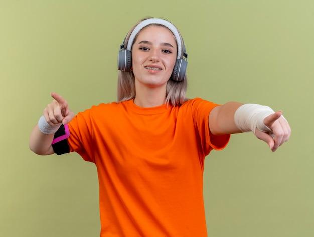 Lächelndes junges kaukasisches sportliches mädchen mit hosenträgern auf kopfhörern, das stirnband und armbänder trägt und mit zwei händen auf die kamera zeigt