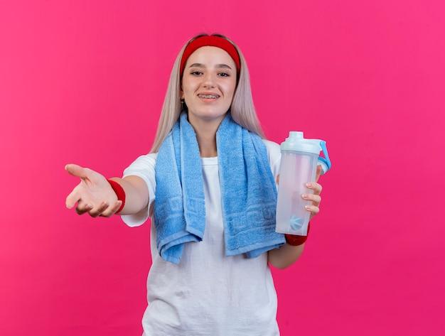 Lächelndes junges kaukasisches sportliches mädchen mit hosenträgern, das stirnband-armbänder trägt und mit handtuch um den hals hält wasserflasche, die die hand ausstreckt