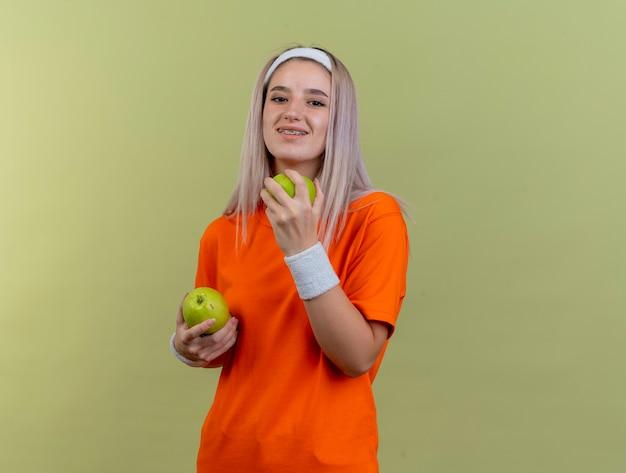 Lächelndes junges kaukasisches sportliches mädchen mit hosenträgern, das stirnband und armbänder trägt, hält äpfel