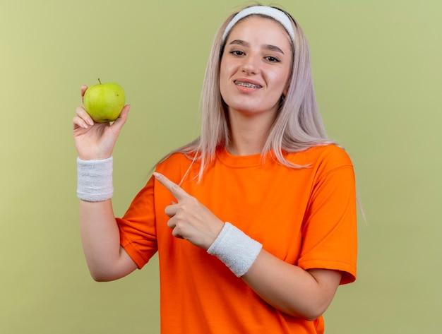 Lächelndes junges kaukasisches sportliches mädchen mit hosenträgern, das stirnband und armbänder trägt, hält und zeigt auf apple
