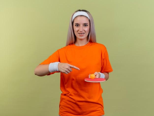 Lächelndes junges kaukasisches sportliches mädchen mit hosenträgern, das stirnband und armbänder trägt, hält und zeigt auf tischtennisball auf schläger