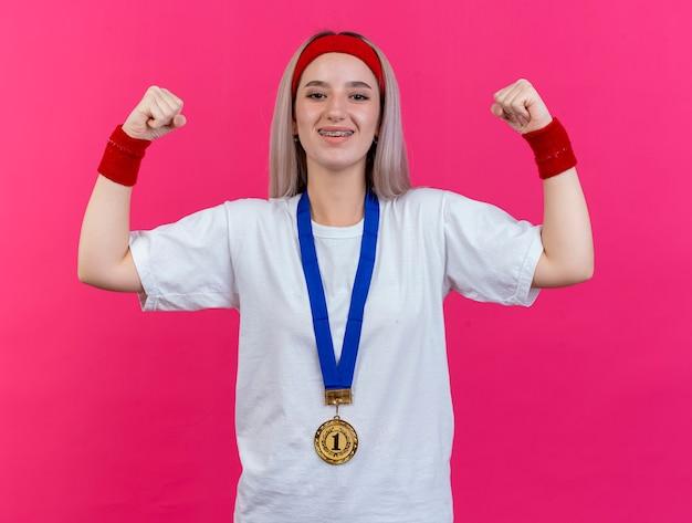 Lächelndes junges kaukasisches sportliches mädchen mit hosenträgern und mit goldmedaille um den hals, das stirnband und armbänder trägt, spannt bizeps an