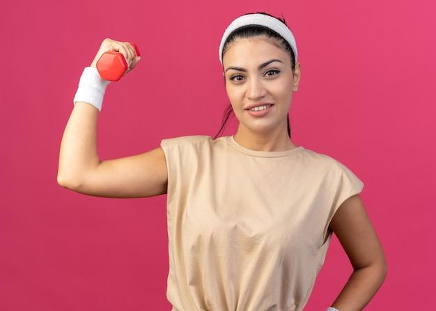 Lächelndes junges, kaukasisches, sportliches mädchen mit stirnband und armbändern, das die hantel anhebt und die hand auf der taille hält, isoliert auf rosa wand