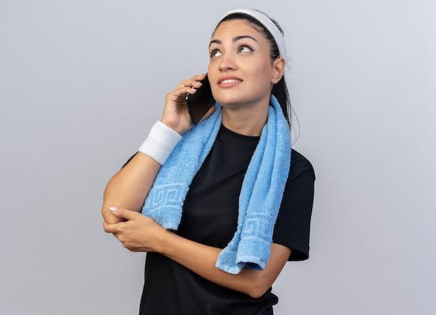 Lächelndes junges kaukasisches sportliches mädchen mit stirnband und armbändern, das mit einem handtuch um den hals telefoniert, isoliert auf weißer wand mit kopienraum nach oben schaut