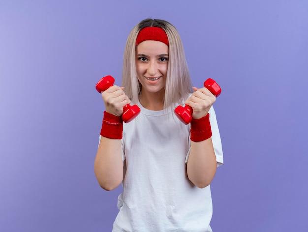 Lächelndes junges kaukasisches sportliches mädchen mit zahnspangen, die stirnband tragen