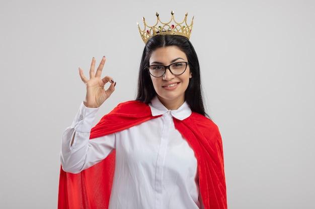 Lächelndes junges kaukasisches superheldenmädchen, das brille und krone trägt, die kamera betrachten, die ok zeichen lokalisiert auf weißem hintergrund mit kopienraum tut
