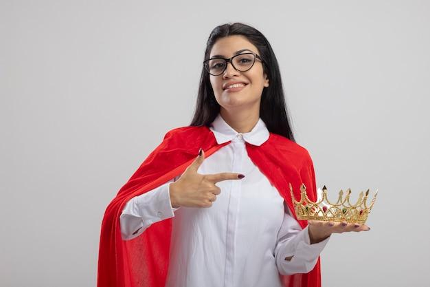 Lächelndes junges kaukasisches superheldenmädchen, das brille und stethoskop hält und auf krone zeigt, die kamera lokalisiert auf weißem hintergrund betrachtet