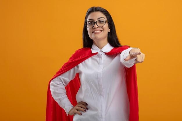 Lächelndes junges kaukasisches superheldenmädchen, das brillen trägt und auf kamera zeigt, die hand auf taille lokalisiert auf orange hintergrund mit kopienraum hält