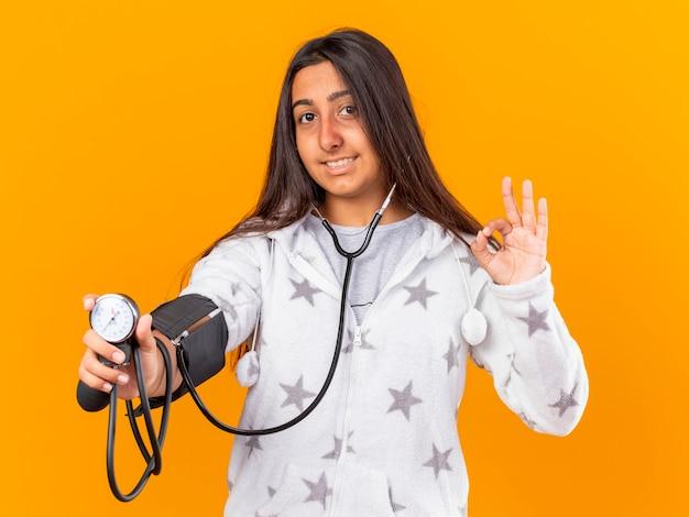 Lächelndes junges krankes mädchen, das ihren eigenen druck mit blutdruckmessgerät misst, das okay geste zeigt, die auf gelbem hintergrund lokalisiert wird