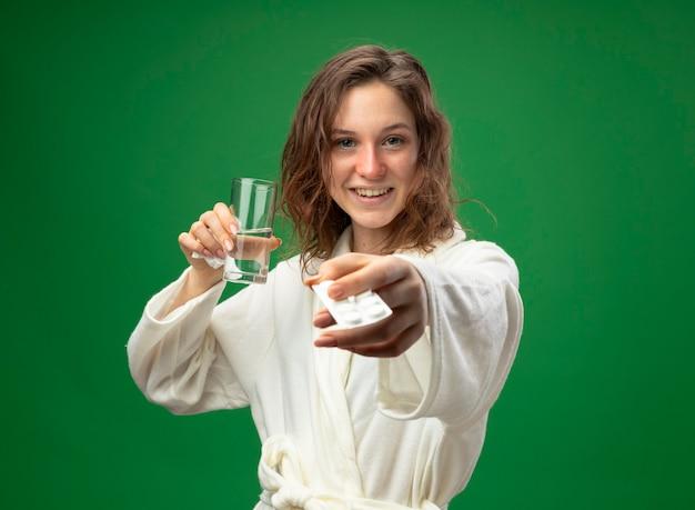 Lächelndes junges krankes mädchen, das weißes gewand trägt, das glas wasser hält und pillen lokalisiert auf grün hält