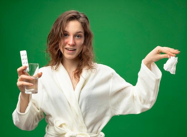 Lächelndes junges krankes mädchen, das weißes gewand trägt glas des wassers mit pillen hält und serviette an der seite lokalisiert auf grün hält