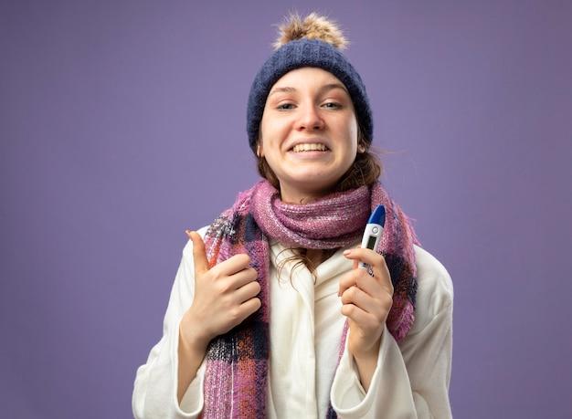 Lächelndes junges krankes mädchen, das weißes gewand und wintermütze mit schal hält thermometer zeigt daumen oben auf lila isoliert