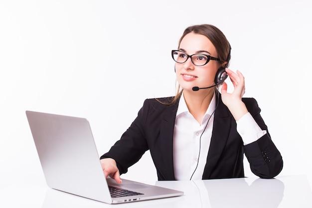 Lächelndes junges kundendienstmädchen mit einem headset an ihrem arbeitsplatz lokalisiert auf weiß