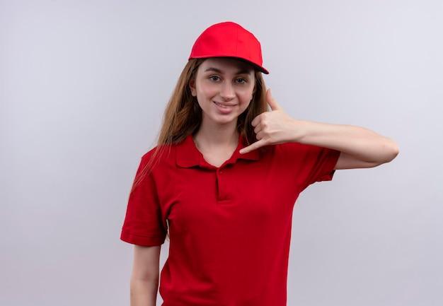 Lächelndes junges liefermädchen, das anrufgeste in der roten uniform auf lokalisiertem weißem raum mit kopienraum tut