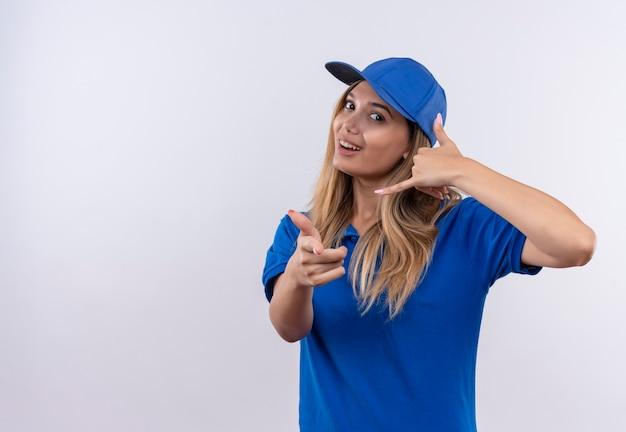 Lächelndes junges liefermädchen, das blaue uniform und kappe trägt, die telefonanrufgeste und sie geste lokalisiert auf weiß zeigt