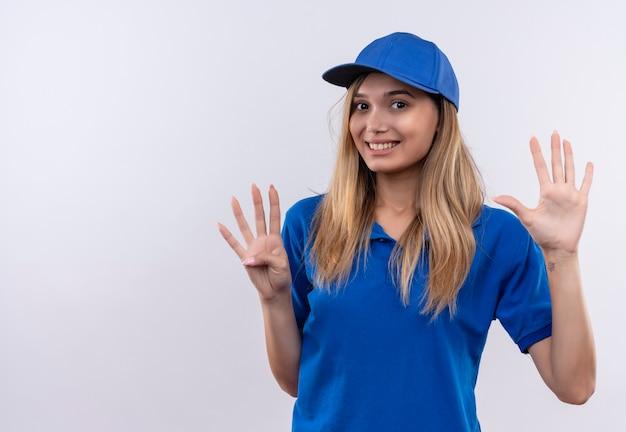 Lächelndes junges liefermädchen, das blaue uniform und kappe trägt, die verschiedene zahlen lokalisiert auf weißer wand mit kopienraum zeigt