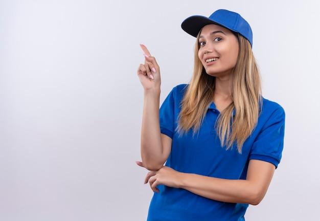 Lächelndes junges liefermädchen, das blaue uniform und kappenpunkte zur seite trägt, lokalisiert auf weißer wand mit kopienraum