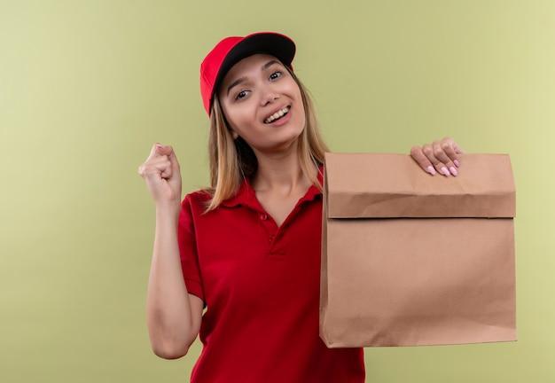 Lächelndes junges liefermädchen, das rote uniform und kappe hält, die papiertüte hält und ja gestikulierte grüne wand zeigt