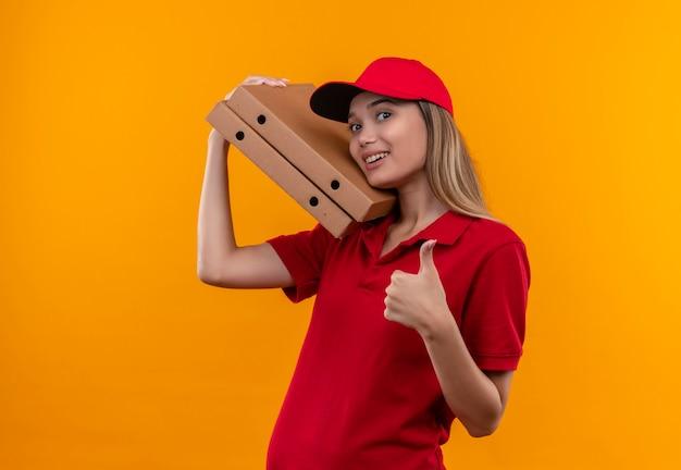 Lächelndes junges liefermädchen, das rote uniform und kappe trägt, die pizzaschachtel auf schulter ihren daumen oben isoliert auf orange wand hält