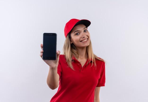 Lächelndes junges liefermädchen, das rote uniform und kappe trägt telefon an kamera lokalisiert auf weiß hält