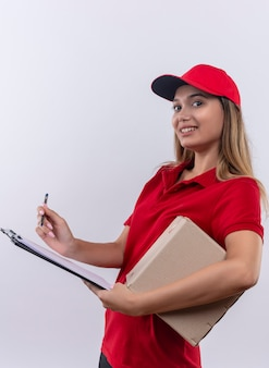 Lächelndes junges liefermädchen, das rote uniform und kappenhaltebox trägt und auf zwischenablage mit stift lokalisiert auf weiß schreibt