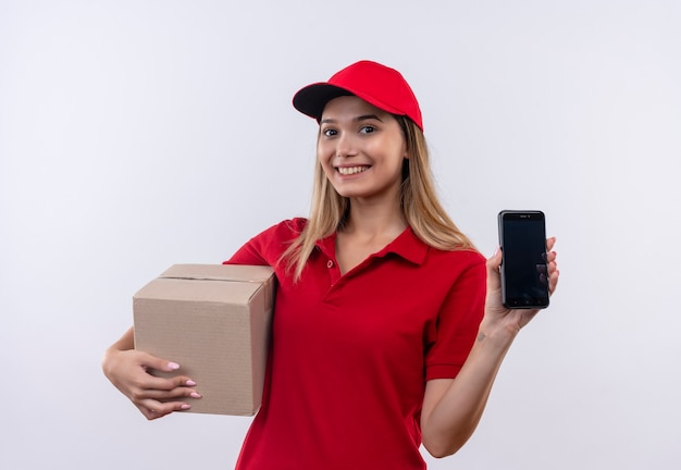 Lächelndes junges liefermädchen, das rote uniform und kappenhaltebox und telefon lokalisiert auf weiß trägt