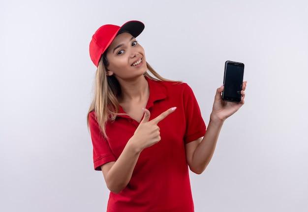 Lächelndes junges liefermädchen, das rote uniform und mützenhaltung trägt und auf telefon lokalisiert auf weiß zeigt