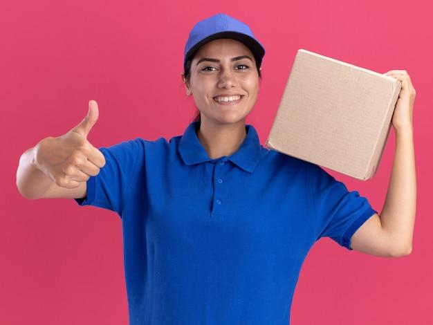 Lächelndes junges liefermädchen, das uniform mit kappe hält box auf schulter trägt und daumen oben auf rosa wand zeigt