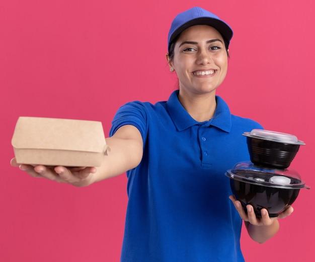 Lächelndes junges liefermädchen, das uniform mit kappe trägt, die lebensmittelbehälter an der front lokalisiert auf rosa wand hält