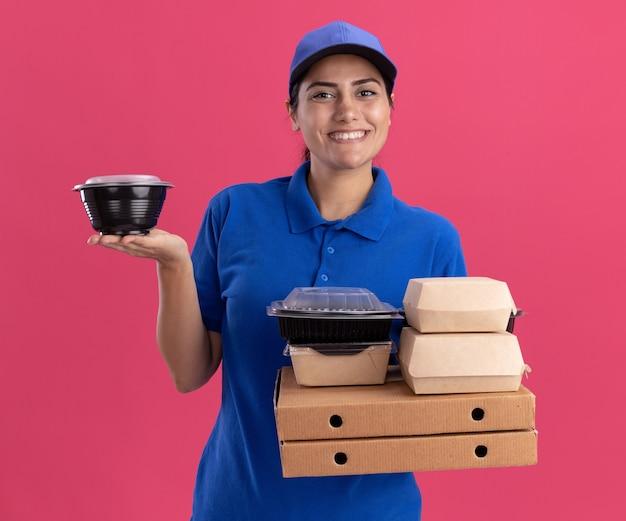Lächelndes junges liefermädchen, das uniform mit kappe trägt, die lebensmittelbehälter auf pizzaschachteln lokalisiert auf rosa wand hält