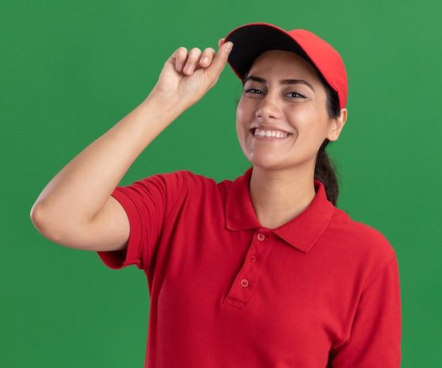 Lächelndes junges liefermädchen, das uniform und kappe hält kappe lokalisiert auf grüner wand trägt