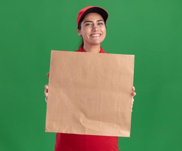 Lächelndes junges liefermädchen, das uniform und kappe trägt, die papiernahrungsmittelpaket an der front lokalisiert auf grüner wand hält