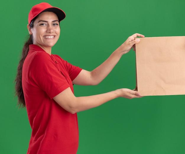 Lächelndes junges liefermädchen, das uniform und kappe trägt, die papiernahrungsmittelpaket an kunden lokalisiert auf grüner wand geben
