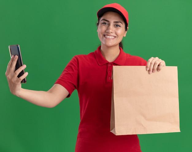 Lächelndes junges liefermädchen, das uniform und kappe trägt, die papiernahrungsmittelpaket mit telefon lokalisiert auf grüner wand hält