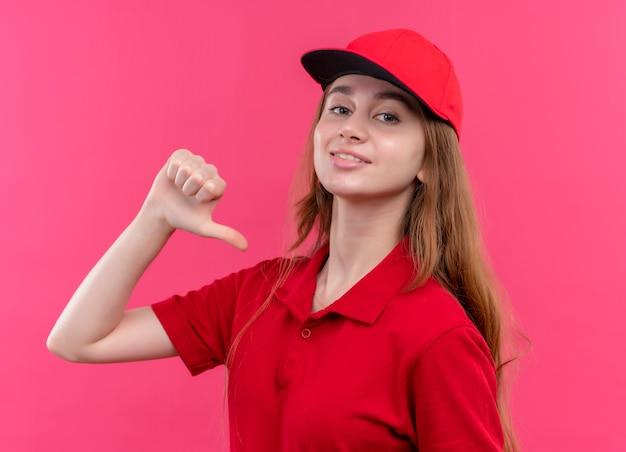 Lächelndes junges liefermädchen in der roten uniform, die auf sich selbst auf der isolierten rosa wand zeigt