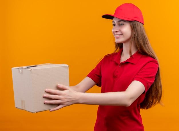 Lächelndes junges liefermädchen in der roten uniform, die kasten an der linken seite auf isolierter orange wand ausdehnt