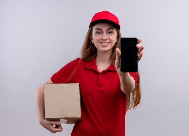 Lächelndes junges liefermädchen in der roten uniform, die kasten hält und handy auf lokalisiertem weißen raum streckt
