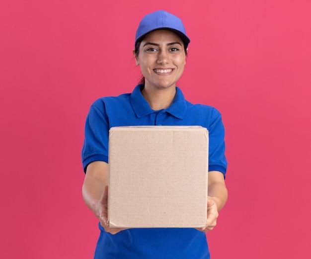 Lächelndes junges liefermädchen in uniform mit mütze, das die box vor der kamera hält, isoliert auf rosa wand pink