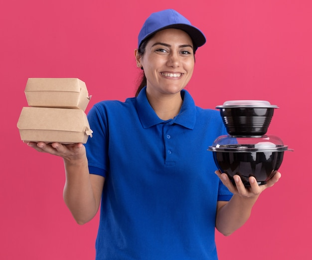 Lächelndes junges liefermädchen in uniform mit mütze mit lebensmittelbehältern isoliert auf rosa wand pink