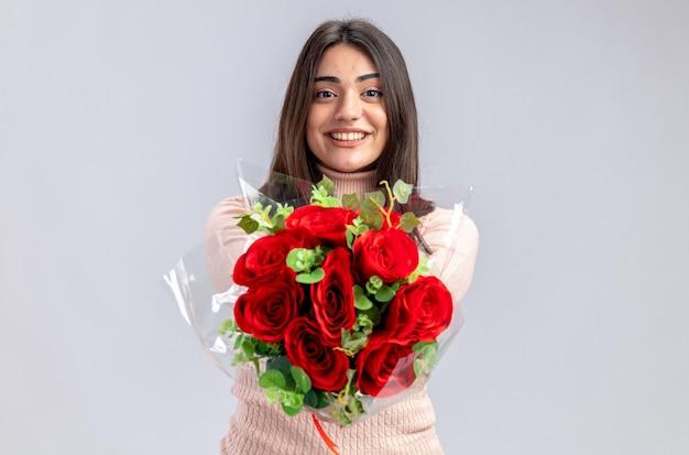Lächelndes junges mädchen am valentinstag, das blumenstrauß in die kamera hält, isoliert auf weißem hintergrund