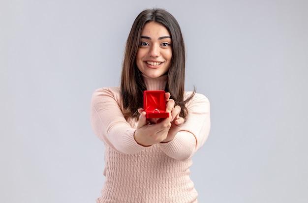 Lächelndes junges mädchen am valentinstag, das ehering in die kamera hält, isoliert auf weißem hintergrund
