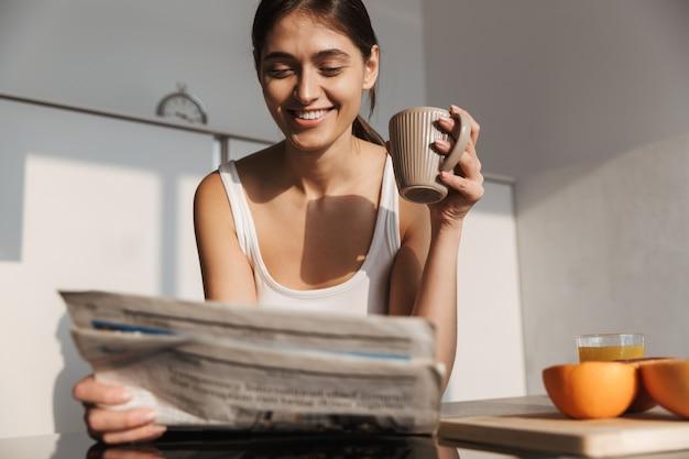 Lächelndes junges mädchen, das am morgen in der küche steht, zeitung liest, tee trinkt