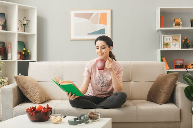 Lächelndes junges mädchen, das auf dem sofa sitzt und ein buch mit einer tasse tee hinter dem couchtisch im wohnzimmer liest?