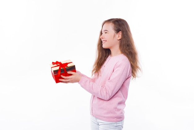 Lächelndes junges mädchen, das eine geschenkbox für jemanden über weißer wand gibt