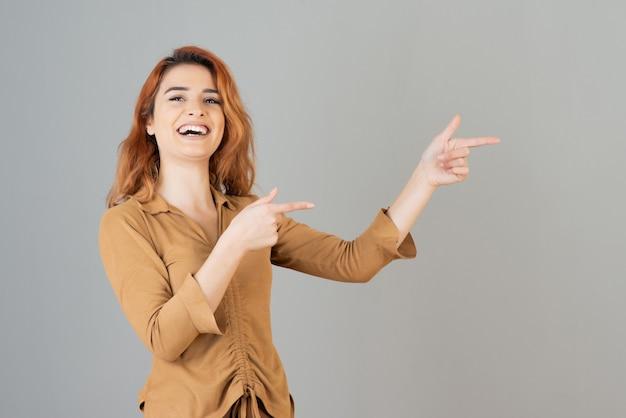 Lächelndes junges mädchen, das ihre finger hochhält und in der grauen wand lacht