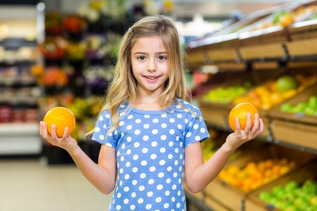 Lächelndes junges mädchen, das orangen hält