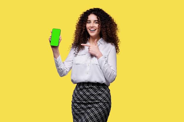 Lächelndes junges mädchen, das smartphone mit leerem grünem bildschirm hält und fingergeste lokalisiert über gelbem hintergrund zeigt