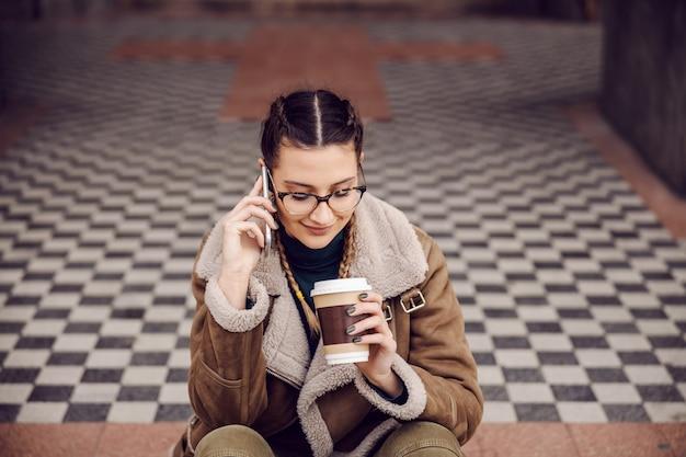 Lächelndes junges mädchen, das vor dem eingang eines alten gebäudes sitzt, einwegbecher mit kaffee hält und telefongespräch führt. wochenendaktivitäten.