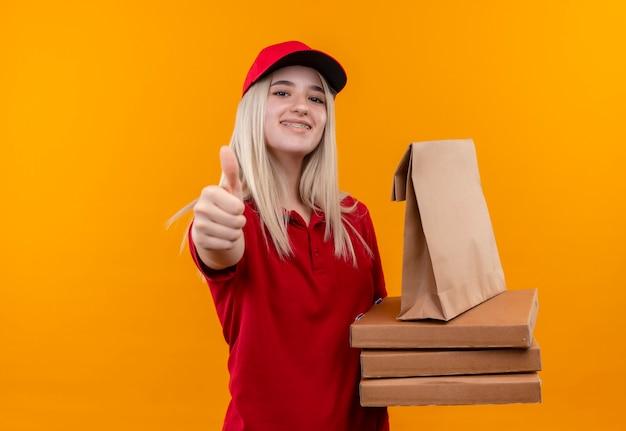 Lächelndes junges mädchen der lieferung, das rotes t-shirt und kappe in der zahnspange trägt, die pizzakiste und papiertasche ihren daumen oben auf lokalisiertem orangefarbenem hintergrund hält